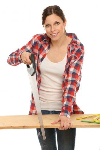 Junge Frau sägt ein Holzbrett