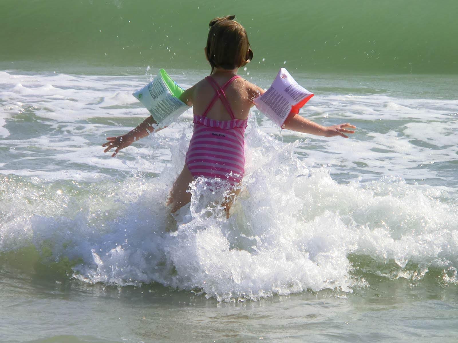 Kind badet im Meer