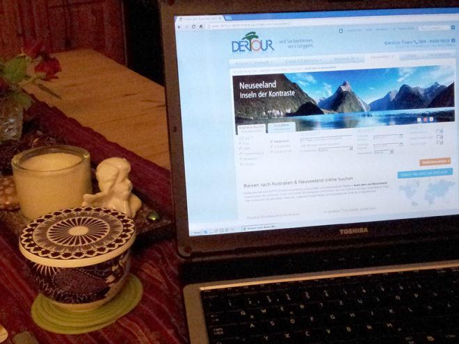 Laptop auf Wohzimmertisch mit Dertour Webseite auf Neuseeland