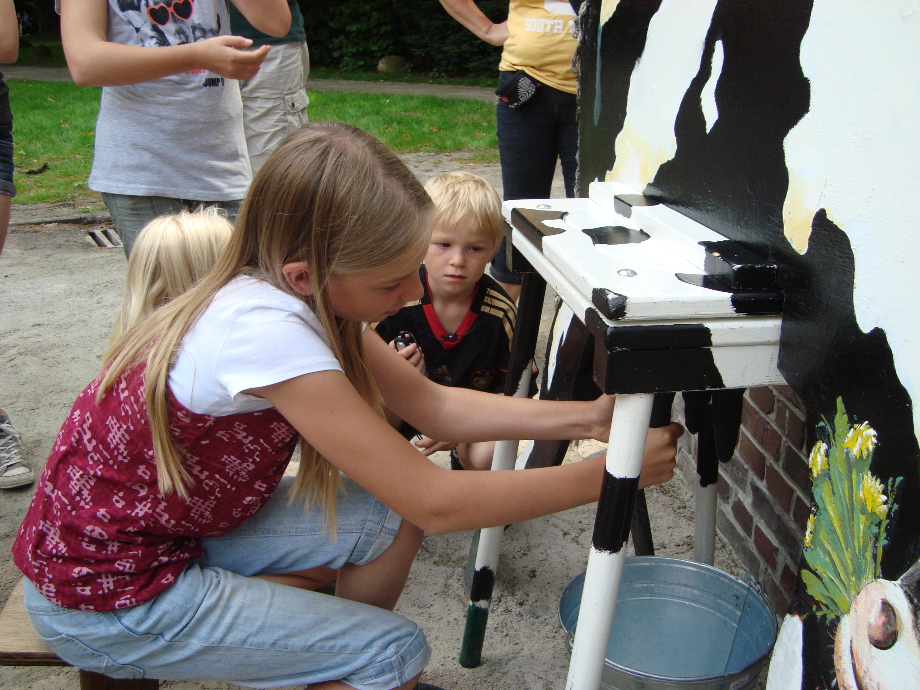 Kinder beim melken der Kuh